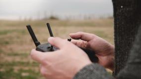 Κινηματογράφηση σε πρώτο πλάνο που πυροβολείται των αρσενικών χεριών που ενεργοποιούν τη μαύρη εναέρια συσκευή ελεγκτών κηφήνων μ απόθεμα βίντεο