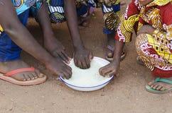 Κινηματογράφηση σε πρώτο πλάνο που πυροβολείται των νέων αφρικανικών αγοριών και των κοριτσιών που τρώνε υπαίθρια Στοκ Φωτογραφία