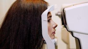 Κινηματογράφηση σε πρώτο πλάνο προσώπου, γυναίκα που κάνει τη δοκιμή ματιών με το tonometer μη επαφών, που το όραμα, ενδοφθάλμια  απόθεμα βίντεο