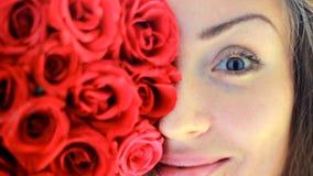 Κινηματογράφηση σε πρώτο πλάνο προσώπου μιας όμορφης νέας γυναίκας με τα κόκκινα τριαντάφυλλα απόθεμα βίντεο