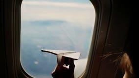 Κινηματογράφηση σε πρώτο πλάνο Σκιαγραφία του χεριού ενός παιδιού με το μικρό αεροπλάνο εγγράφου στα πλαίσια του παραθύρου αεροπλ φιλμ μικρού μήκους