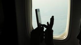 Κινηματογράφηση σε πρώτο πλάνο σκοτεινή σκιαγραφία των χεριών παιδιών και του κινητού τηλεφώνου ενάντια στο φωτιστικό του αεροπλά απόθεμα βίντεο
