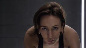 Κινηματογράφηση σε πρώτο πλάνο της αρκετά ελκυστικής νέας γυναίκας που απολαμβάνει το workout της στο ποδήλατο άσκησης πρόσωπο κο φιλμ μικρού μήκους