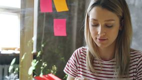Κινηματογράφηση σε πρώτο πλάνο της αρκετά νέας γυναίκας με τα ξανθά μαλλιά που κολλούν τα χρωματισμένα υπομνήματα στον πίνακα γυα απόθεμα βίντεο
