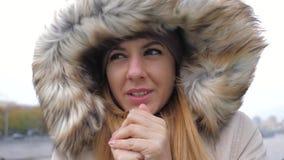 Κινηματογράφηση σε πρώτο πλάνο της γυναίκας σε ένα σακάκι με την κουκούλα έκλεισε από τον ισχυρό κρύο αέρα