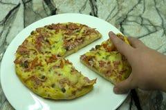 Κινηματογράφηση σε πρώτο πλάνο της γυναίκας που μαζεύει με το χέρι τη φέτα της τυροειδούς πίτσας μοτσαρελών στο ξύλινο τηγάνι στο Στοκ Εικόνες