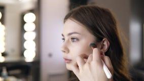 Κινηματογράφηση σε πρώτο πλάνο της γυναίκας brunette που εφαρμόζει το καλλυντικό στα ζυγωματικά με έναν τύπο επάνω στη βούρτσα Το φιλμ μικρού μήκους