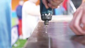 Κινηματογράφηση σε πρώτο πλάνο της διάτρησης χεριών του εργαζομένου που σφίγγει τη βίδα στον ξύλινο πίνακα στο στάδιο r Παγκόσμιο απόθεμα βίντεο