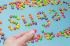 Κινηματογράφηση σε πρώτο πλάνο της διατροφής ζάχαρης καραμέλας καραμελών που σχεδιάζεται, στο μπλε υπόβαθρο Στοκ Φωτογραφία