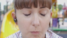 Κινηματογράφηση σε πρώτο πλάνο της ελκυστικής καυκάσιας ομιλίας γυναικών στο τηλέφωνο μέσω της ασύρματης κάσκας υπαίθρια απόθεμα βίντεο