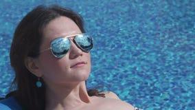 Κινηματογράφηση σε πρώτο πλάνο της ηλιοθεραπείας γυναικών κοντά στη λίμνη, μπλε υπόβαθρο νερού απόθεμα βίντεο