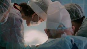 Κινηματογράφηση σε πρώτο πλάνο της ιατρικής ομάδας στο στάδιο της εκτέλεσης μιας χειρουργικής επέμβασης στο νοσοκομείο φιλμ μικρού μήκους