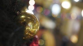 Κινηματογράφηση σε πρώτο πλάνο της κίτρινης σφαίρας Χριστουγέννων στο χριστουγεννιάτικο δέντρο με το θολωμένο υπόβαθρο φιλμ μικρού μήκους