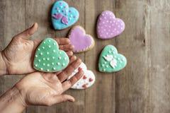 Κινηματογράφηση σε πρώτο πλάνο της καρδιάς μπισκότων στο λούστρο στα χέρια μιας γυναίκας στοκ εικόνες