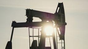 Κινηματογράφηση σε πρώτο πλάνο της λειτουργώντας αντλίας πετρελαίου στο υπόβαθρο του ήλιου Στοκ φωτογραφία με δικαίωμα ελεύθερης χρήσης