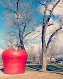 Κινηματογράφηση σε πρώτο πλάνο της μεγάλης κόκκινης Apple με το πράσινο ορόσημο φύλλων στο πάρκο πόλεων την ηλιόλουστη χειμερινή  Στοκ εικόνα με δικαίωμα ελεύθερης χρήσης