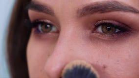 Κινηματογράφηση σε πρώτο πλάνο της νέας γυναίκας brunette που εφαρμόζει τη σκόνη προσώπου σε σε αργή κίνηση απόθεμα βίντεο