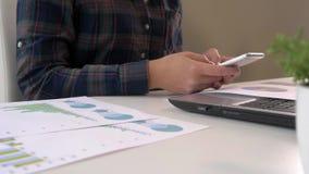 Κινηματογράφηση σε πρώτο πλάνο της νέας εργασίας επιχειρησιακών γυναικών στο εσωτερικό γραφείων στο smartphone εκμετάλλευσης PC κ απόθεμα βίντεο