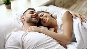 Κινηματογράφηση σε πρώτο πλάνο της νέας συζήτησης και του αγκαλιάσματος όμορφων και ζευγών αγάπης στο κρεβάτι ξυπνώντας το πρωί Στοκ Φωτογραφίες