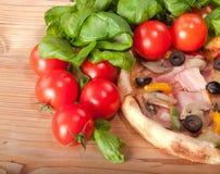 Κινηματογράφηση σε πρώτο πλάνο της πίτσας με τις ντομάτες, το τυρί και το βασιλικό στην ξύλινη ανασκόπηση Στοκ Εικόνες
