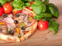 Κινηματογράφηση σε πρώτο πλάνο της πίτσας με τις ντομάτες, το τυρί και το βασιλικό στην ξύλινη ανασκόπηση Στοκ Εικόνα