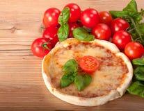 Κινηματογράφηση σε πρώτο πλάνο της πίτσας με τις ντομάτες, το τυρί και το βασιλικό στην ξύλινη ανασκόπηση Στοκ εικόνες με δικαίωμα ελεύθερης χρήσης