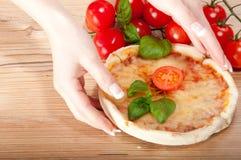 Κινηματογράφηση σε πρώτο πλάνο της πίτσας με τις ντομάτες, το τυρί, το basi και της γυναίκας handsl στην ξύλινη ανασκόπηση Στοκ φωτογραφίες με δικαίωμα ελεύθερης χρήσης