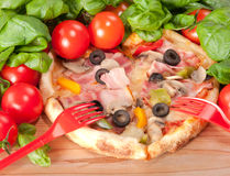 Κινηματογράφηση σε πρώτο πλάνο της πίτσας με το κόκκινους δίκρανο, τις ντομάτες, το τυρί και το βασιλικό στην ξύλινη ανασκόπηση Στοκ Εικόνα