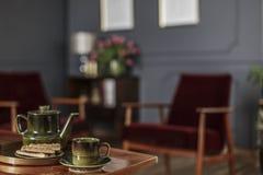 Κινηματογράφηση σε πρώτο πλάνο της πράσινης κανάτας, του φλυτζανιού τσαγιού και των μπισκότων που τοποθετούνται στον πίνακα στο θ Στοκ Φωτογραφία
