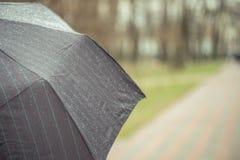 Κινηματογράφηση σε πρώτο πλάνο της σκοτεινής ομπρέλας κατά τη διάρκεια της βροχής Στοκ Εικόνα