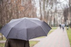 Κινηματογράφηση σε πρώτο πλάνο της σκοτεινής ομπρέλας κατά τη διάρκεια της βροχής Στοκ εικόνα με δικαίωμα ελεύθερης χρήσης