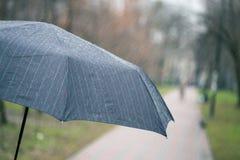 Κινηματογράφηση σε πρώτο πλάνο της σκοτεινής ομπρέλας κατά τη διάρκεια της βροχής Στοκ Εικόνες