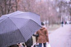 Κινηματογράφηση σε πρώτο πλάνο της σκοτεινής ομπρέλας κατά τη διάρκεια της βροχής Στοκ Φωτογραφίες