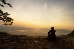 Κινηματογράφηση σε πρώτο πλάνο της συνεδρίασης γυναικών ήρεμα του απότομου βράχου και εξέταση την κοιλάδα και τα βουνά Στοκ φωτογραφία με δικαίωμα ελεύθερης χρήσης