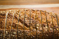 Κινηματογράφηση σε πρώτο πλάνο της τεμαχισμένης φραντζόλας ολόκληρου του ψωμιού σιταριού Στοκ εικόνα με δικαίωμα ελεύθερης χρήσης