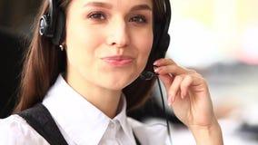Κινηματογράφηση σε πρώτο πλάνο της χαμογελώντας γυναίκας που λειτουργεί σε ένα τηλεφωνικό κέντρο ο άγγελος ως όμορφη επιχειρηματί απόθεμα βίντεο