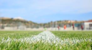 Κινηματογράφηση σε πρώτο πλάνο της χρωματισμένης γραμμής ορίου ενός πράσινου αγωνιστικού χώρου ποδοσφαίρου Στοκ Εικόνες