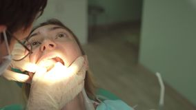 Κινηματογράφηση σε πρώτο πλάνο της όμορφης γυναίκας στην οδοντική καρέκλα με τη νέα επιθεώρηση οδοντιάτρων και τον ειδικό φωτισμό απόθεμα βίντεο