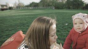 Κινηματογράφηση σε πρώτο πλάνο της όμορφης κατανάλωσης έφηβη στα κινεζικά νουντλς φύσης με chopsticks που κάθονται στο μαλακό κόκ φιλμ μικρού μήκους