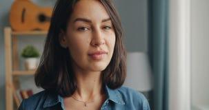 Κινηματογράφηση σε πρώτο πλάνο της όμορφης κυρίας που εξετάζει το παράθυρο που γυρίζει έπειτα στο χαμόγελο καμερών απόθεμα βίντεο