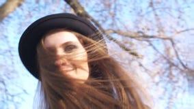 Κινηματογράφηση σε πρώτο πλάνο της όμορφης νέας γυναίκας σε ένα σκοτεινό καπέλο και του μαύρου σακακιού δέρματος με το μοντέρνο m απόθεμα βίντεο