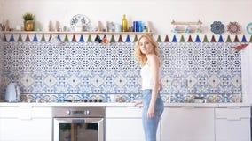 Κινηματογράφηση σε πρώτο πλάνο της όμορφης νέας γυναίκας με τα ξανθά μαλλιά στην άσπρη μπλούζα και το τζιν παντελόνι που κατασκευ στοκ εικόνα