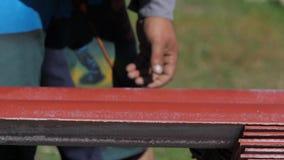 Κινηματογράφηση σε πρώτο πλάνο του άνδρα εργαζόμενος στα λειτουργώντας ενδύματα που παίρνουν έναν κατάλογο κόκκινου υλικού κατασκ φιλμ μικρού μήκους