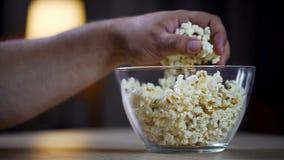 Κινηματογράφηση σε πρώτο πλάνο του αρσενικού χεριού που παίρνει popcorn από το κύπελλο στον πίνακα, ανθυγειινός εξαρτημένος τροφί στοκ εικόνες