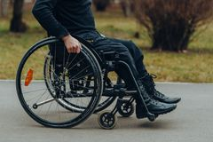Κινηματογράφηση σε πρώτο πλάνο του αρσενικού χεριού στη ρόδα της αναπηρικής καρέκλας κατά τη διάρκεια του περιπάτου στο πάρκο στοκ εικόνα