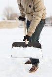 Κινηματογράφηση σε πρώτο πλάνο του ατόμου που φτυαρίζει το χιόνι από driveway Στοκ Φωτογραφία
