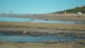 Κινηματογράφηση σε πρώτο πλάνο του βρώμικου νερού αποβλήτων και της μολυσμένης άμμου με τους ανθρώπους που χαλαρώνουν εδώ κοντά φιλμ μικρού μήκους