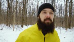 Κινηματογράφηση σε πρώτο πλάνο του γενειοφόρου αθλητή στο κίτρινο παλτό που τρέχει στο χιονώδες χειμερινό δάσος απόθεμα βίντεο