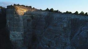 Κινηματογράφηση σε πρώτο πλάνο του γκρίζου απότομου βράχου βουνών τοπ που καλύπτει με τα κωνοφόρα δέντρα ενάντια στο μπλε ουρανό  φιλμ μικρού μήκους