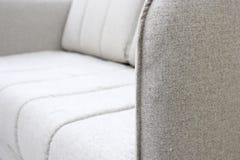 Κινηματογράφηση σε πρώτο πλάνο του γκρίζου καναπέ με armrest τα κλωστοϋφαντουργικά προϊόντα, νέο σύγχρονο σχέδιο επίπλων Με ελεύθ στοκ εικόνα